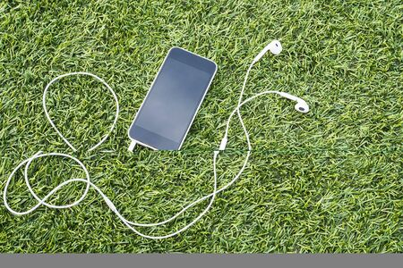 Mobile phone with head phone on green artificial grass 免版税图像