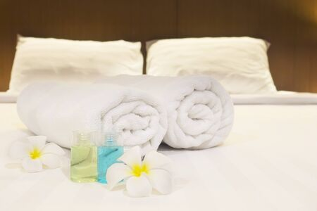 Hotel towel with flower and shampoo and soap bottle set on white bed 免版税图像