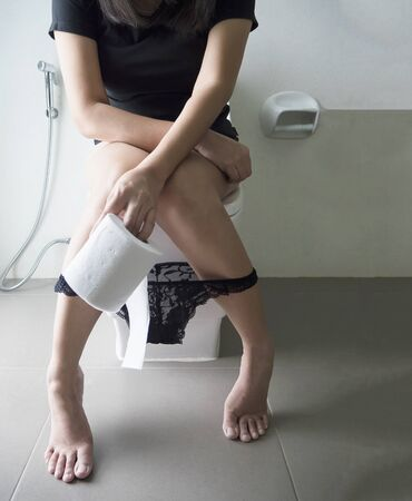Woman sitting on toilet bowl holding tissue paper  - health problem concept