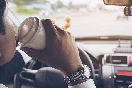 Man eating donuts with coffee while driving car - multitasking unsafe driving concept 免版税图像