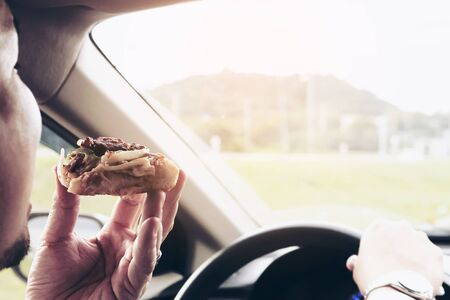 Business man eating pizza while driving a car dangerously