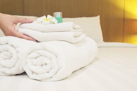 Lady set up white towel set on bed in hotel room 免版税图像