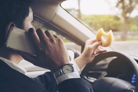 Man rush driving car using mobile and eat fast food dangerously