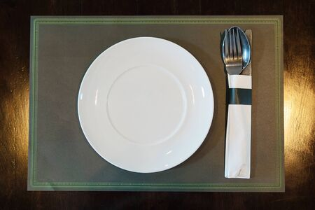 White plate with spoon knife set on a mat in restaurant 免版税图像