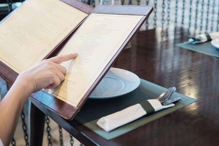 Woman is choosing food in a menu to order in restaurant 免版税图像