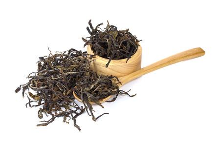 gunpowder tea: dry tea in wooden bowls. Isolated on white background Stock Photo