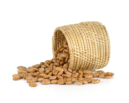 toppled: spill the beans - pinto beans spilled from basket isolated on white background