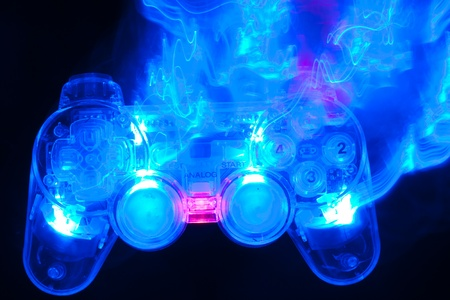 computer gaming: The blue game controller on a black background Stock Photo