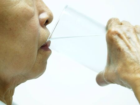 old woman drinking water isolated against white background