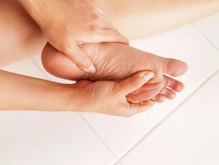 tahriş: kadın ağrıyan ayak kontrol eder Stok Fotoğraf