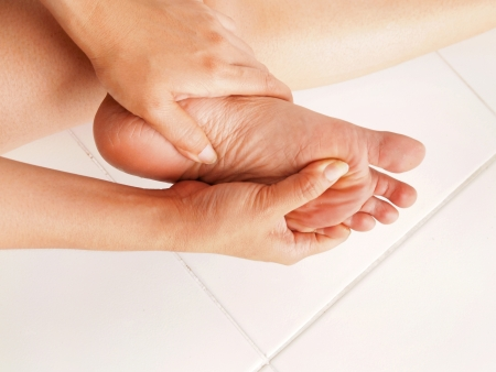 lesionado: mujer mira su pie dolorido Foto de archivo