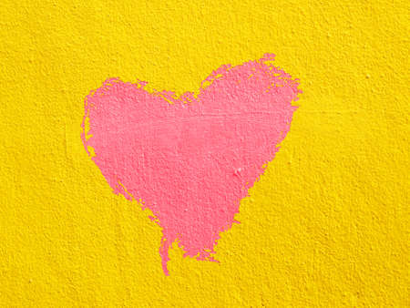 red heart on  yellow cement wall photo
