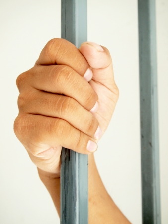 hands behind bars  Stock Photo - 24043754