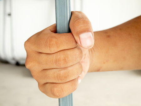 clutching: Hands clutching bars