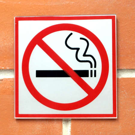 permitted: Sign hangs on a brick wall warning that smoking is not permitted in the area
