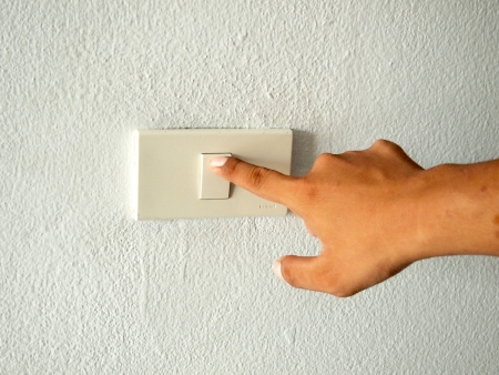 hand with finger on light switch photo