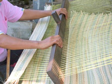 Thai woman hands weaving reed mat  photo