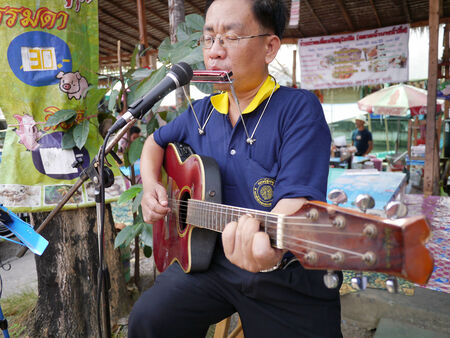 SAMUTPRAKRAN, THAILAND - FEBRUARY 11 :Unidentified street musician plays guitar at walking street market in Samutprakran,Thailand on February 11, 2012
