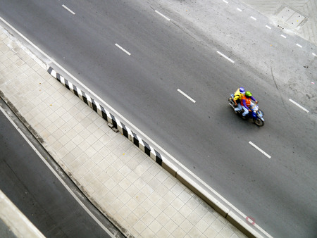 BANGKOK, THAILAND - MARCH 3: unidentified riding by motorbike on March 3, 2012 in Bangkok, Thailand. Motorbike is the most popular and available transportation in South Asia
