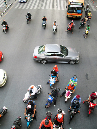 BANGKOK - NOV 17: Motorcyclists and cars wait at a junction during rush hour on Nov 17, 2012 in Bangkok, Thailand. Motorcycles are often the transport of choice for Bangkoks heavily congested roads.