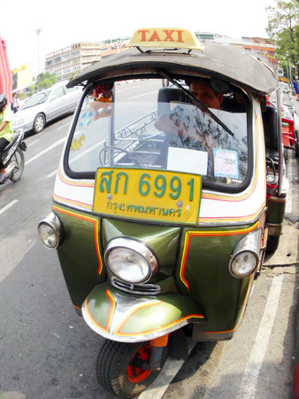 mototaxi: BANGKOK - JANUARY 4: Tuk-tuk moto taxi on the street in the Wat suthat area on January 4, 2012 in Bangkok. Famous bangkok moto-taxi called tuk-tuk is a landmark of the city and popular transport