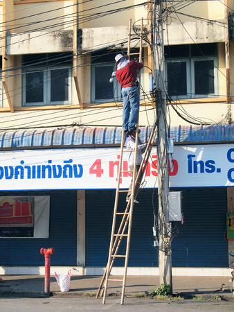 LOP BURI, Thailand - DEMCEMBER 8, 2012  Two Thai electricians are fixing confusing electricity lines on a pole
