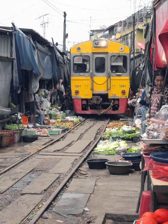 MAEKLONG, THAILAND - SEPTEMBER 7: The famous railway markets at Maeklong, Thailand, September 7, 2013, Samut Songkhram, Thailand.Three times a day the train runs through these stalls.