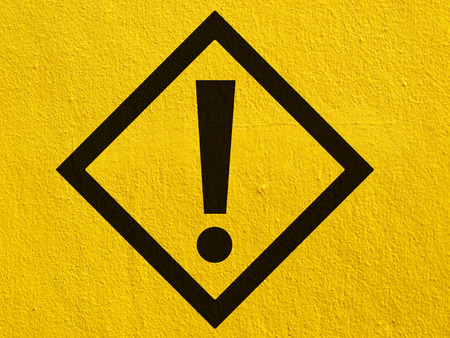 safety signs: a black warning attention sign points painted on a stucco wall outside