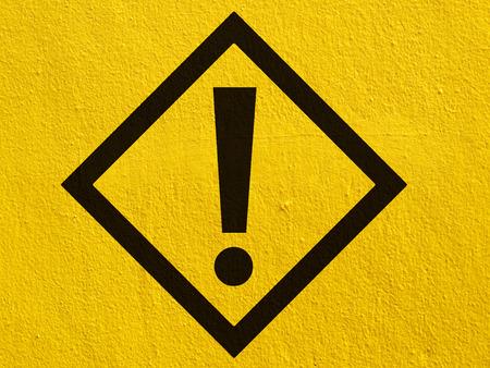 advertencia: una advertencia negras atención letrero señala pintadas en una pared de estuco exterior Foto de archivo