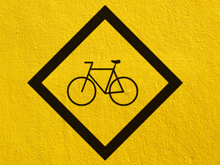 stucco wall: a black Bicycle points painted on a stucco wall outside