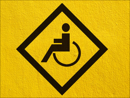 stucco wall: a black disabled sign painted on a stucco wall outside