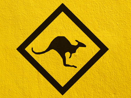 a black Kangaroo Sign painted on a stucco wall outside photo