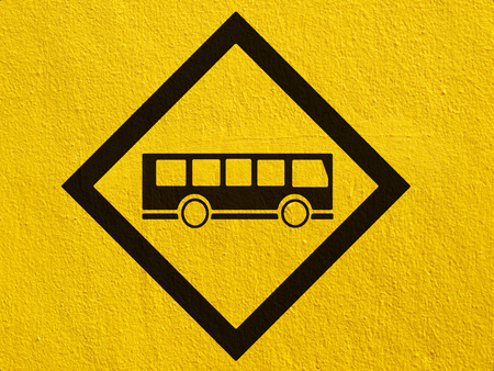 stucco wall: a black Bus Stop Sign painted on a stucco wall outside