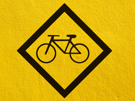 a black Bike sign painted on a stucco wall outside photo