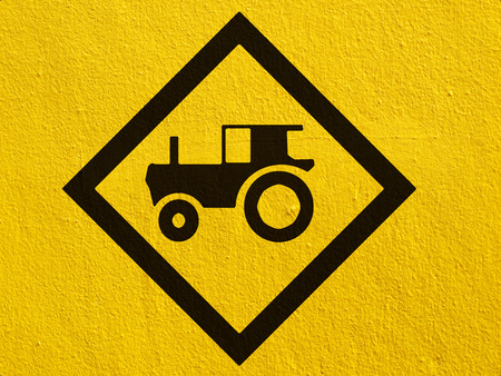 tractor crossing warning traffic sign painted on a stucco wall outside photo