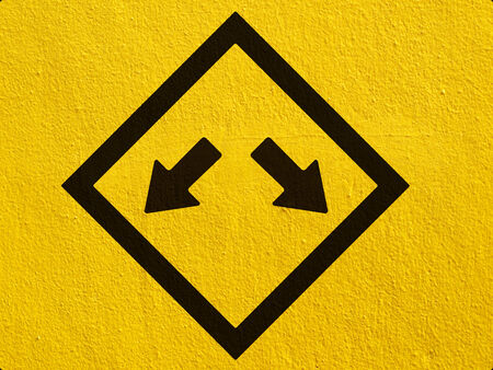 either: traffic sign indicating pass on either side painted on a stucco wall outside Stock Photo