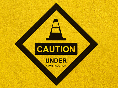 Caution Under Construction Traffic Sign painted on a stucco wall outside Standard-Bild