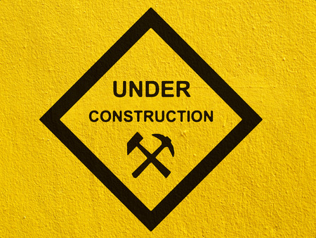 stucco wall: under construction road sign painted on a stucco wall outside
