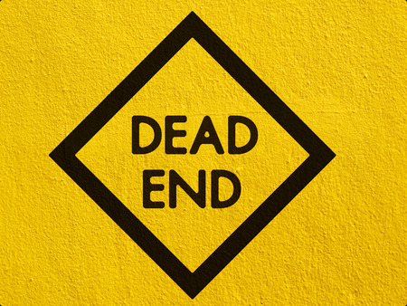 Dead End Sign painted on a stucco wall outside photo