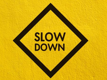 znak drogowy: Slow Down żółty znak drogowy namalowany na ścianie stiuk zewnątrz