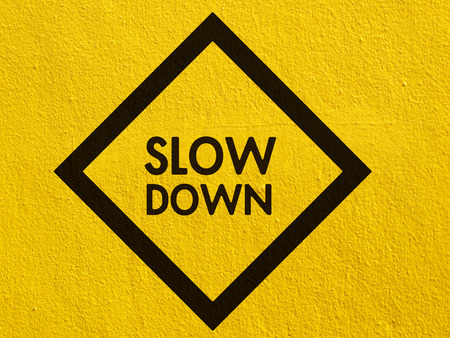 Slow Down yellow road sign painted on a stucco wall outside