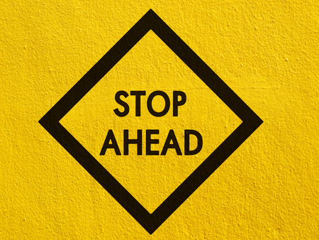 stucco wall: Stop ahead sign painted on a stucco wall outside Stock Photo