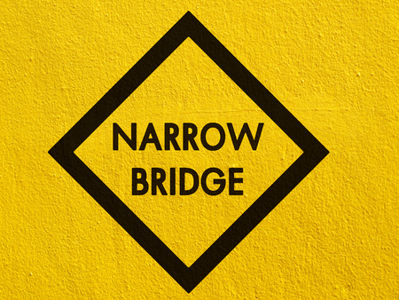 Narrow bridge Sign painted on a stucco wall outside photo