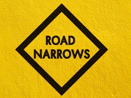 stucco wall: road narrows sign painted on a stucco wall outside Stock Photo