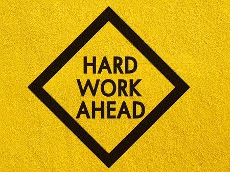 hard work: Hard work ahead street sign painted on a stucco wall outside