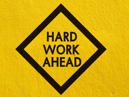 disco duro: Placa de la calle por delante el trabajo duro pintado en una pared de estuco exterior