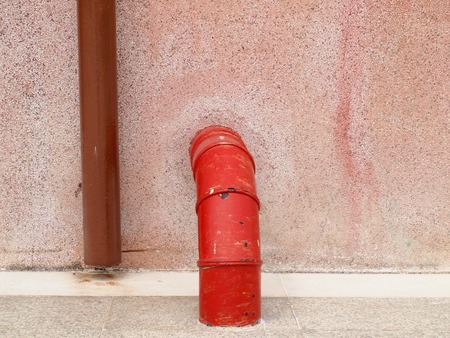 plumbing pipe against stucco wall , industrial grunge  photo