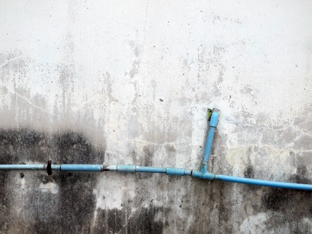 plumbing pipe against stucco wall , industrial grunge background photo