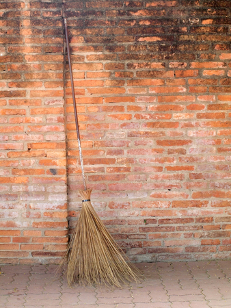 slovenly: Old obsolete broom or besom leaning on the brick wall Stock Photo