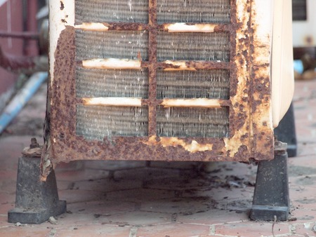 conditioned: Old rusty air conditioner outdoor unit on house facade